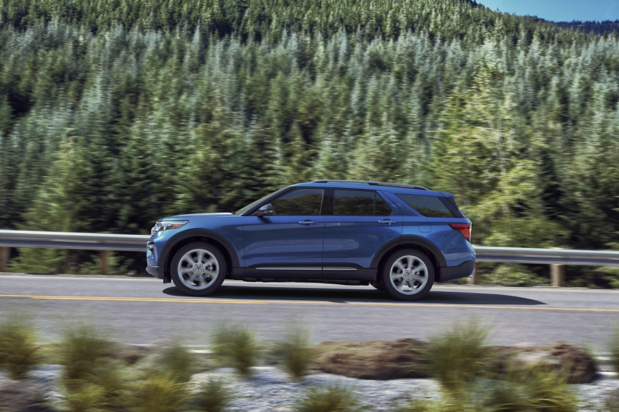 Side view of a Ford Explorer Limited Hybrid Platinum in Atlas Blue driving along a tree lined highway
