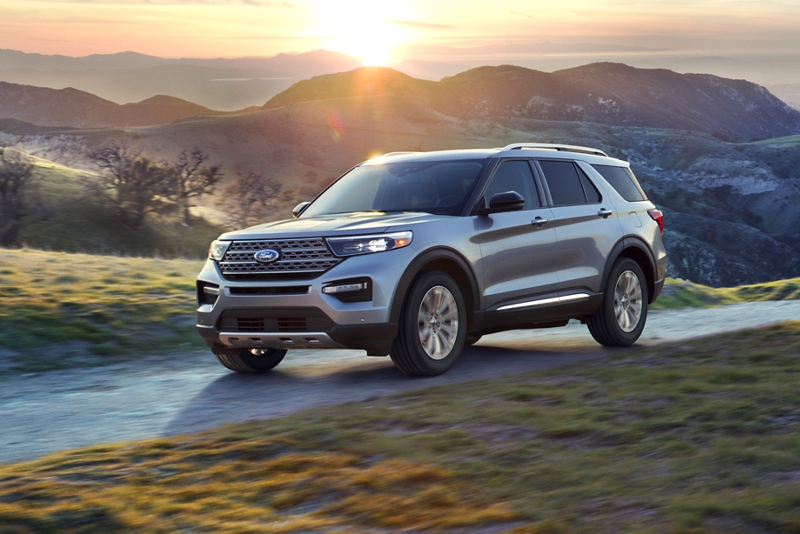Front three quarter view of a Ford Explorer Limited Hybrid being driven on a rural mountain road at sunset