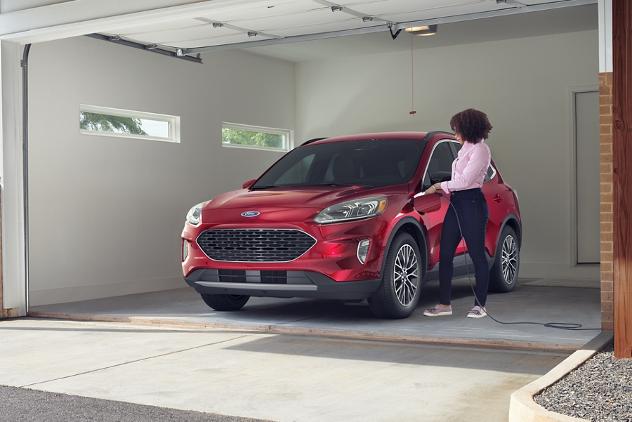 Front view of a woman standing in a garage near a parked Ford Escape Plug In Hybrid