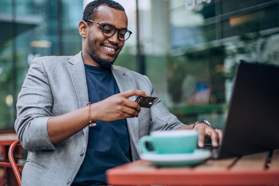 Man on his laptop sitting at a café looking at his FordPass Visa
