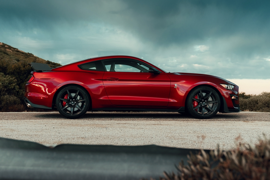 Side view of 2020 Ford Mustang G T 500 on dirt road in front of hill