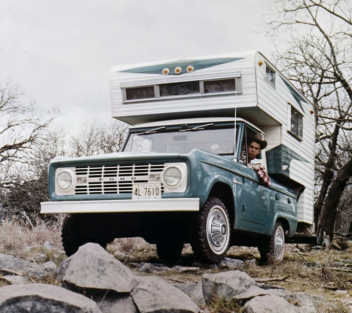 A 1967 Ford Bronco in Peacock Blue with a Camper Body being driven over rocky terrain