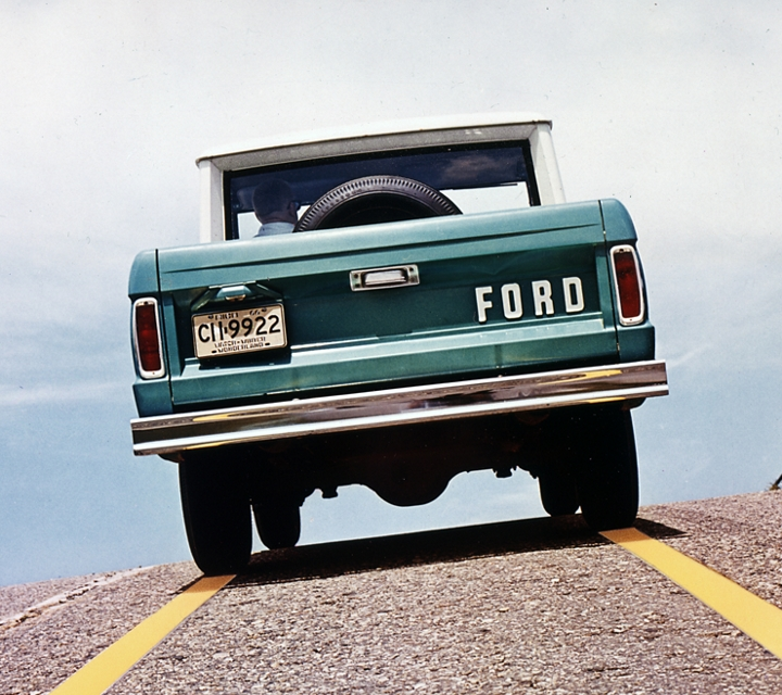 Rear view of a 1967 Ford Bronco being driven up a hill