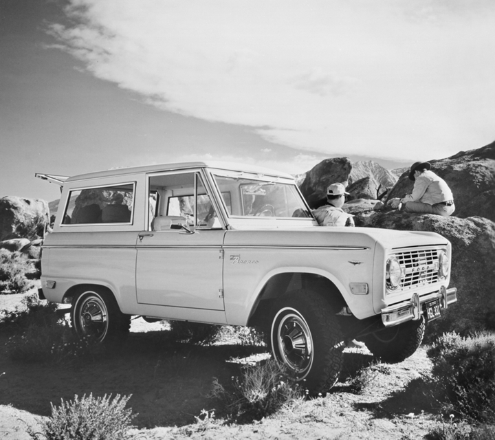 A black and white image of two people sitting around a 1968 Ford Bronco Sport Wagon