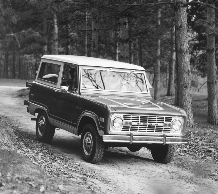 A black and white image of a 1973 Ford Bronco Ranger on a wooded trail