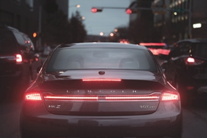 A Lincoln M K Z is stopped at a light in heavy traffic as the red brake lights and traffic light illuminate brightly in the night