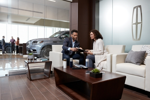 A woman is sitting and discussing business with a service representative in a beautifully appointed meeting room inside a Lincoln Dealership