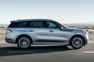 A Lincoln Aviator is being driven through a desert highway during the day
