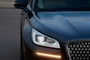 The front end of a Lincoln vehicle shows illuminated headlights and a turn signal that shines bright in the night