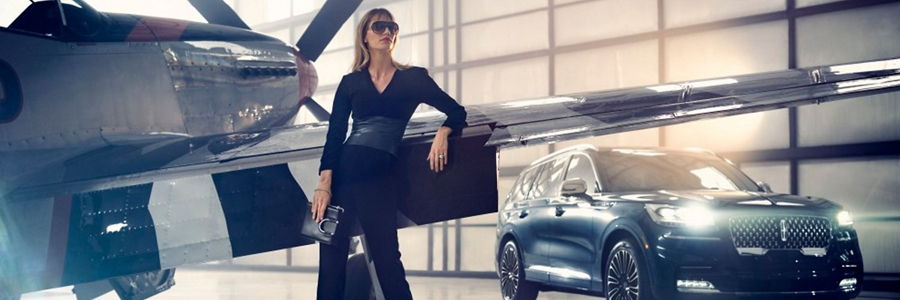 A fashionably dressed woman is standing near an airplane inside a private hangar