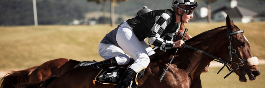A jockey is seen riding a horse to help capture the spirit of the Thoroughbred theme