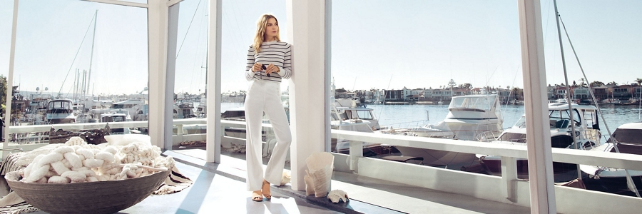 A woman is looking out toward the marina from inside of an expansive Yacht Club with large windows white materials and an airy open design