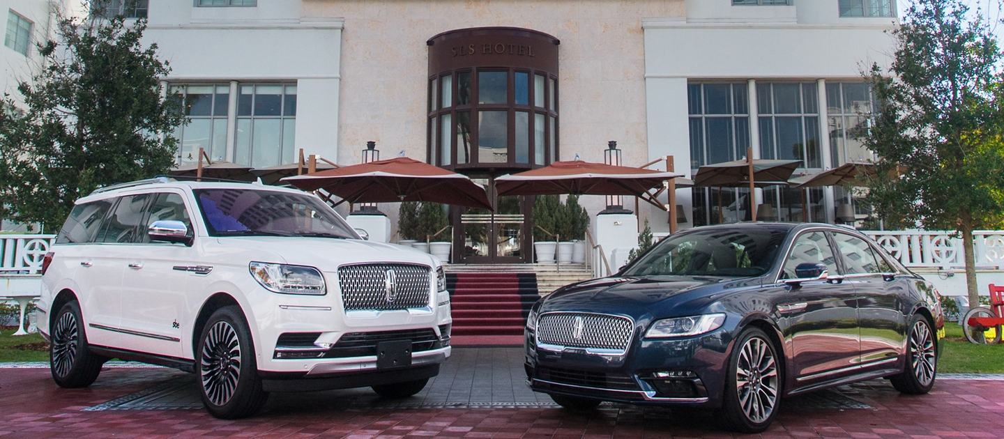 Lincoln vehicles shown in front of hotel