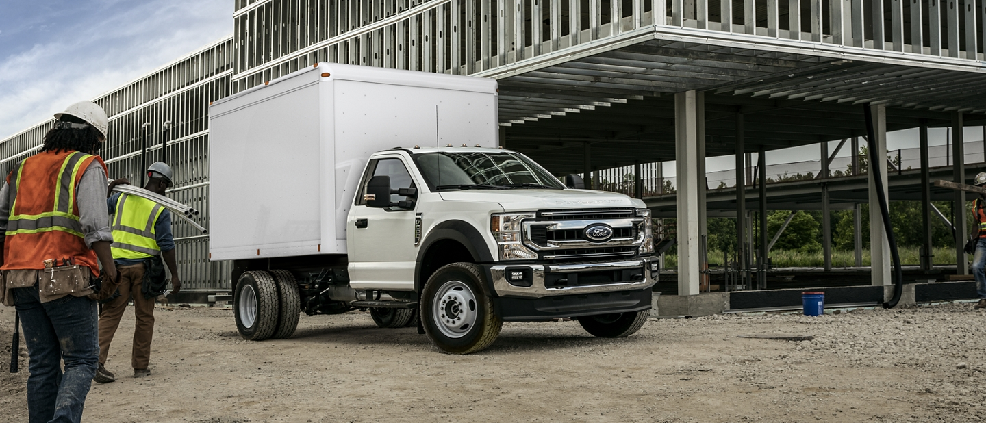 Workers approaching 2020 Ford Super Duty Chassis Cab F 600 in Oxford White with box upfit parked at construction site