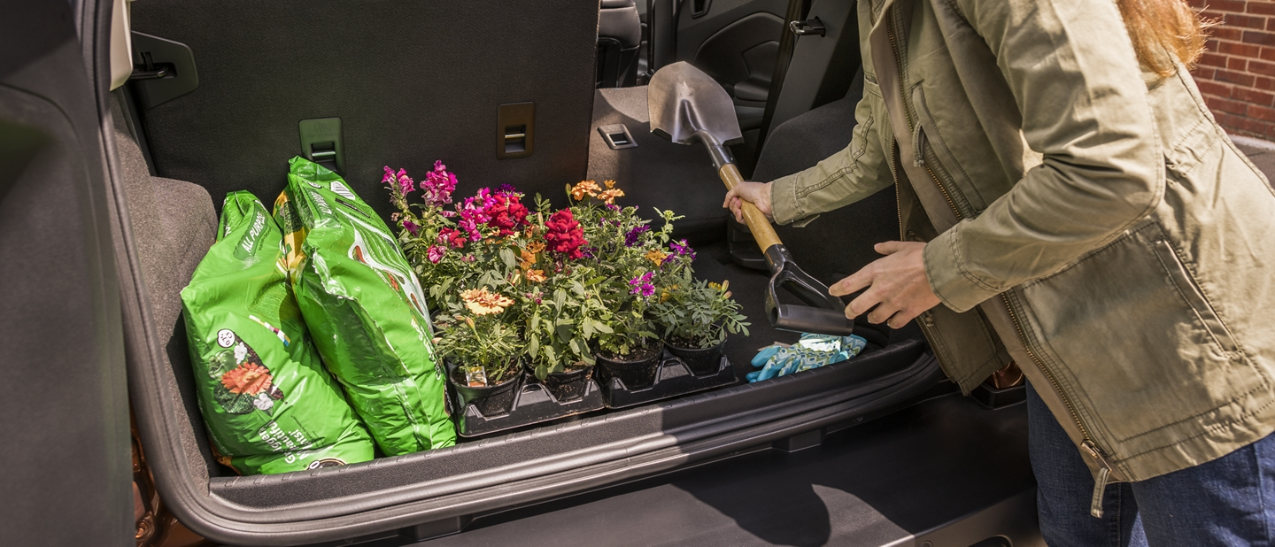 Woman utilizing an EcoSports cargo area with second row seats folded to create more space for her garden supplies