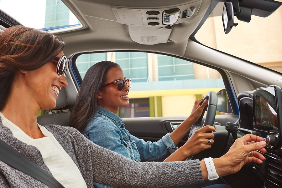 Two women in a 2019 Ford EcoSport using the controls on the centre console to highlight