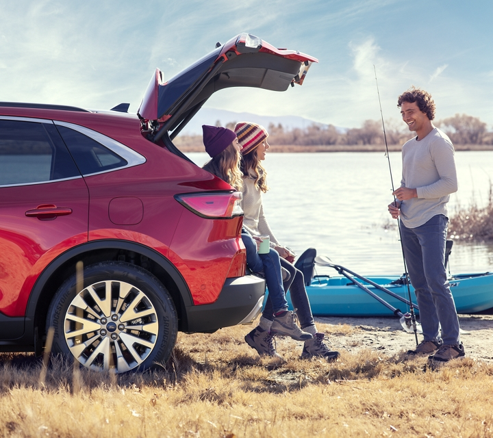 2020 Ford Escape Titanium gas model in Rapid Red with a young family by a lake