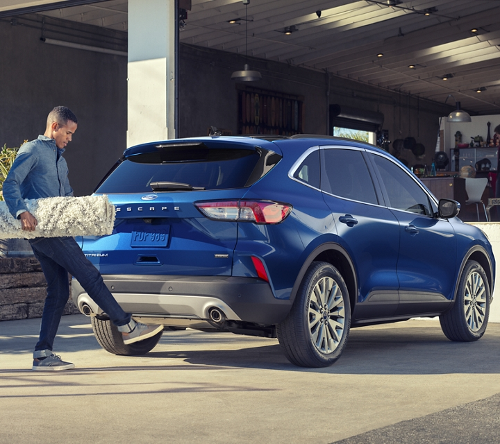A young couple using the hands free foot activated liftgate to load their 2020 Ford Escape Titanium Hybrid