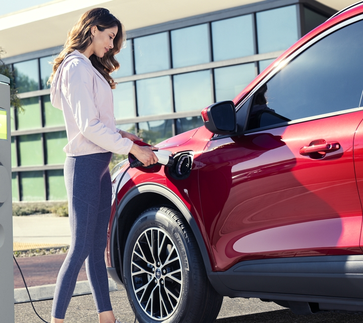 Woman at a public station charging a 2020 Ford Escape Plug in Hybrid in Rapid Red