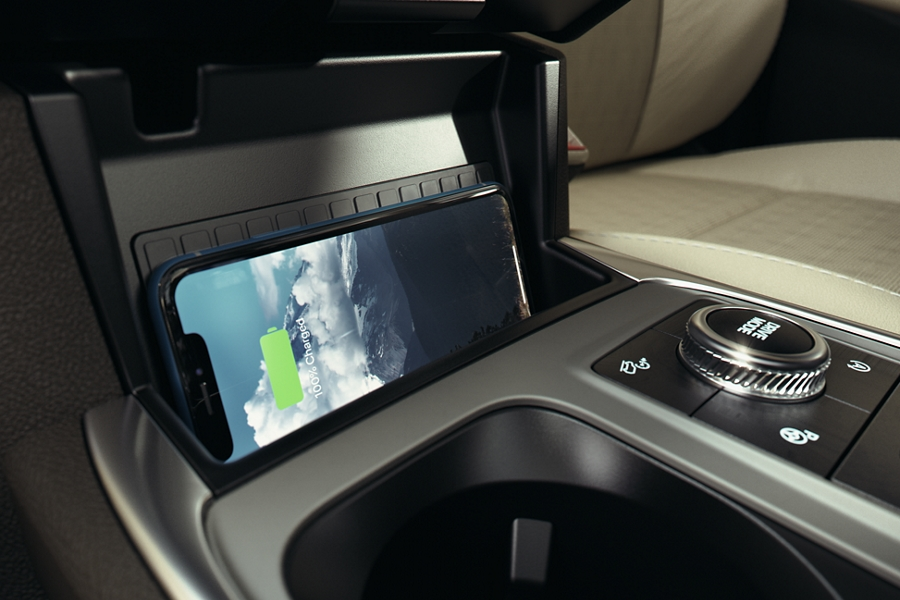 An iPhone laid sideways on the available wireless charging pad in the centre console of a 2020 Explorer