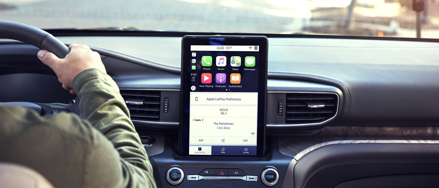 A person in the drivers seat of a 2020 Explorer using the 8 inch L E D touchscreen