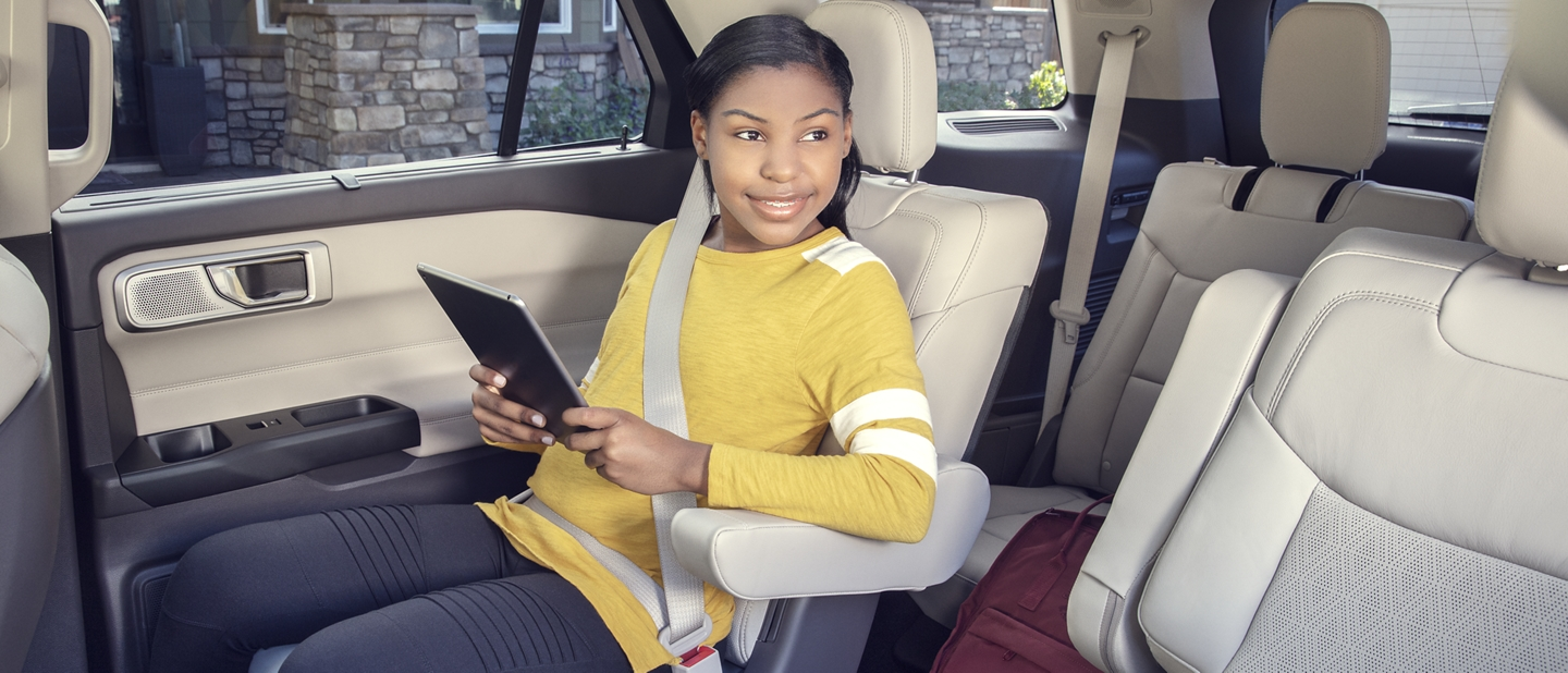 A girl sitting in the second row using a tablet