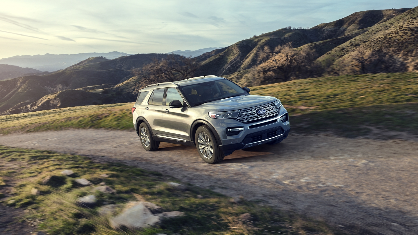 A 2020 Explorer Limited in Iconic Silver driving up a steep hill