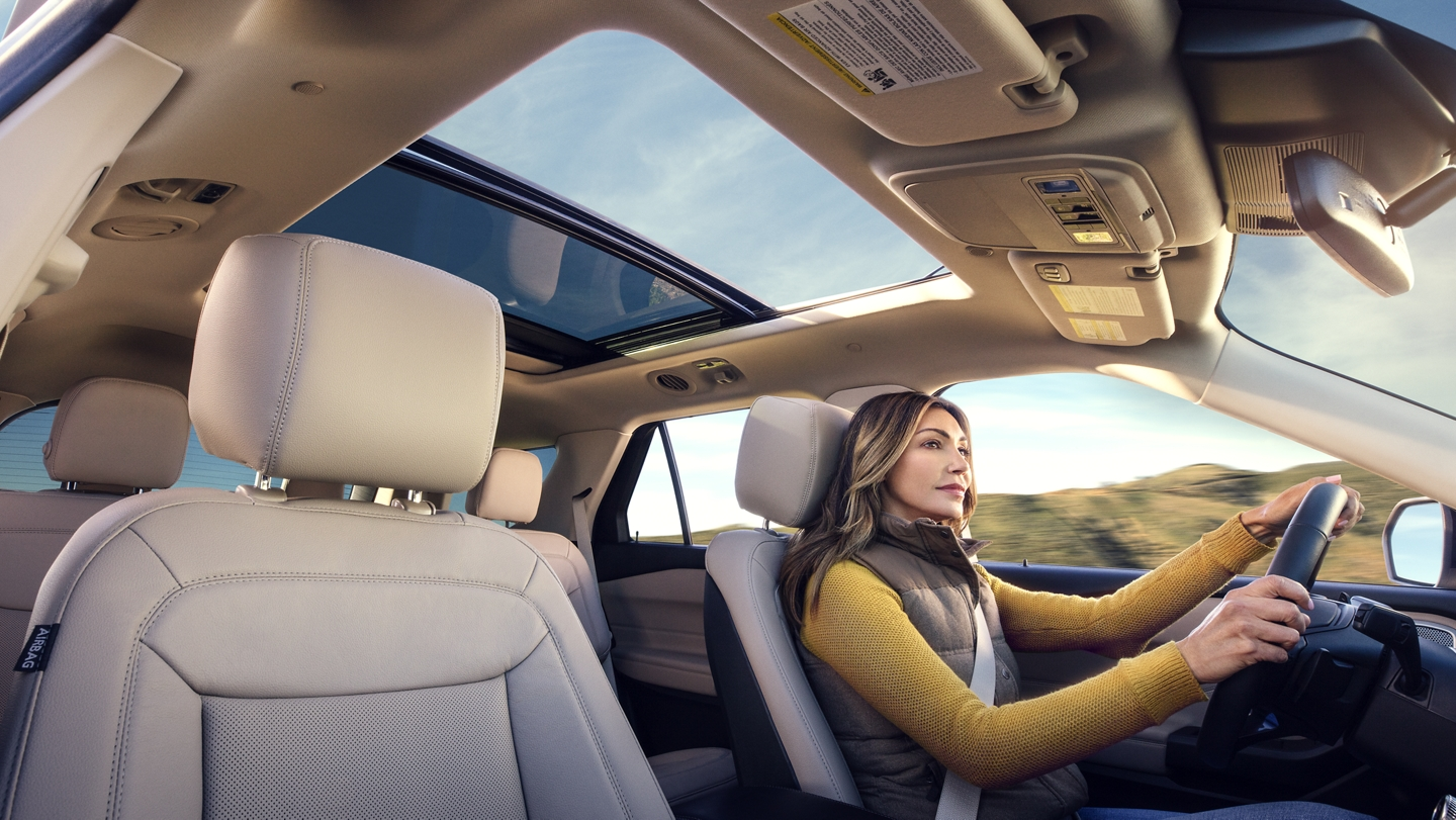 A woman driving a 2020 Explorer with a twin panel moonroof