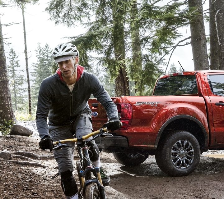 Ranger parked in a forest with a man on bike riding away from the vehicle