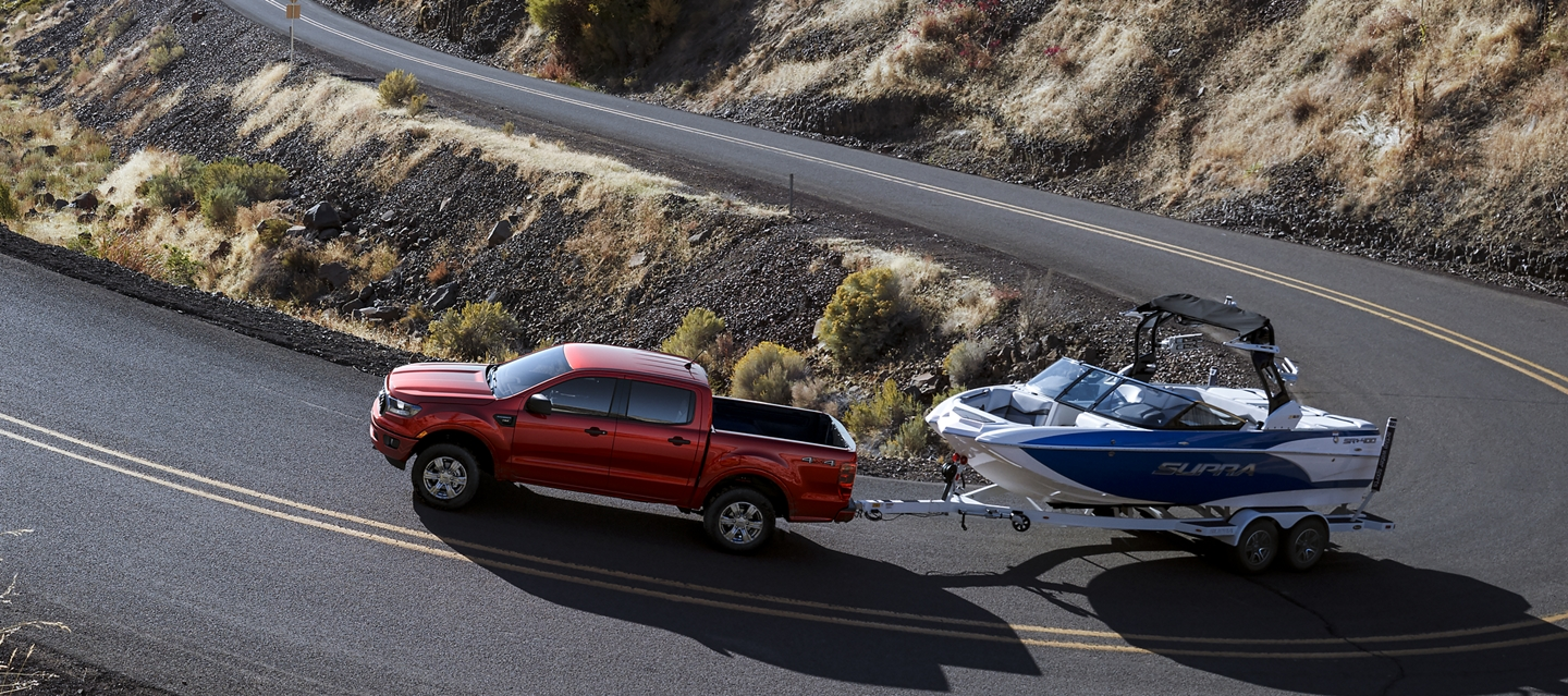 A Ranger is towing a boat up a curvy mountain pass