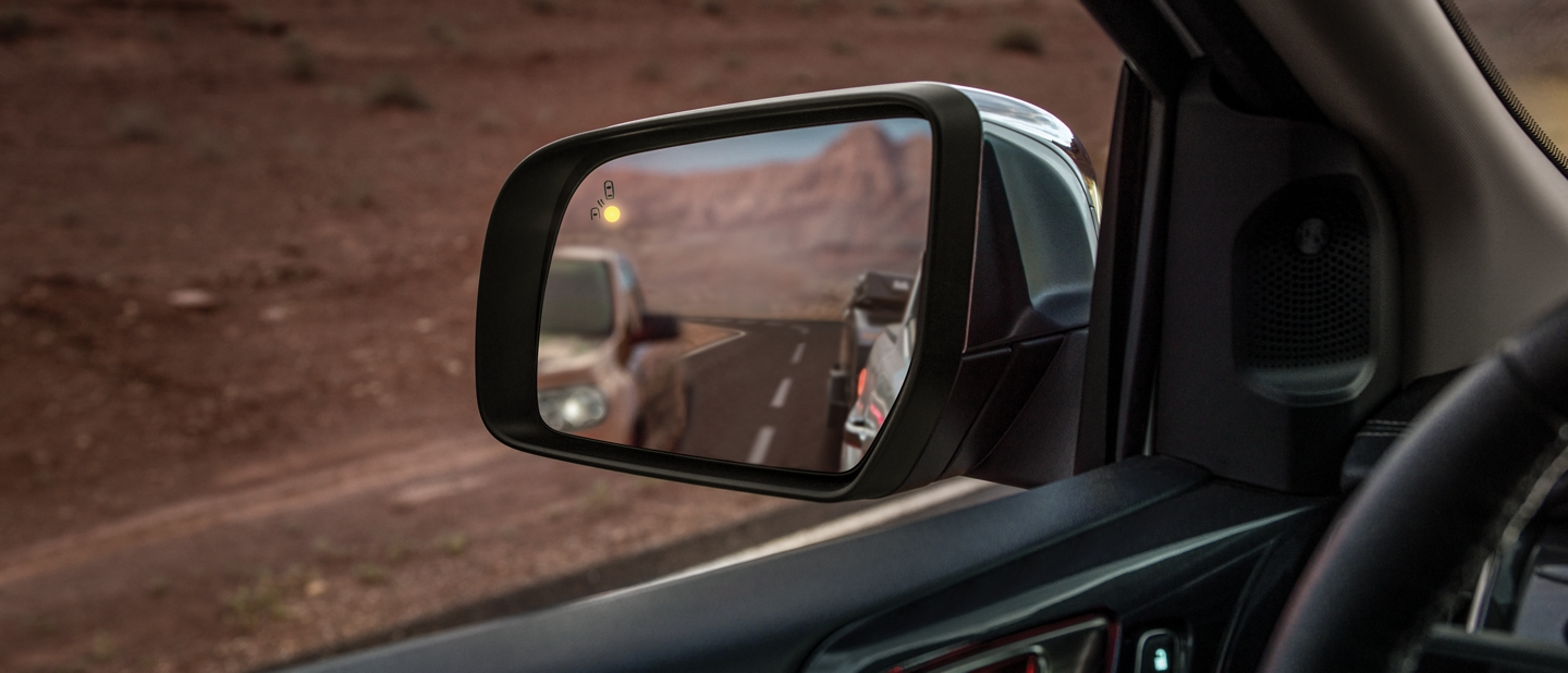Close up image of a side view mirror with the BLIS light on indicating someone is in your blind spot