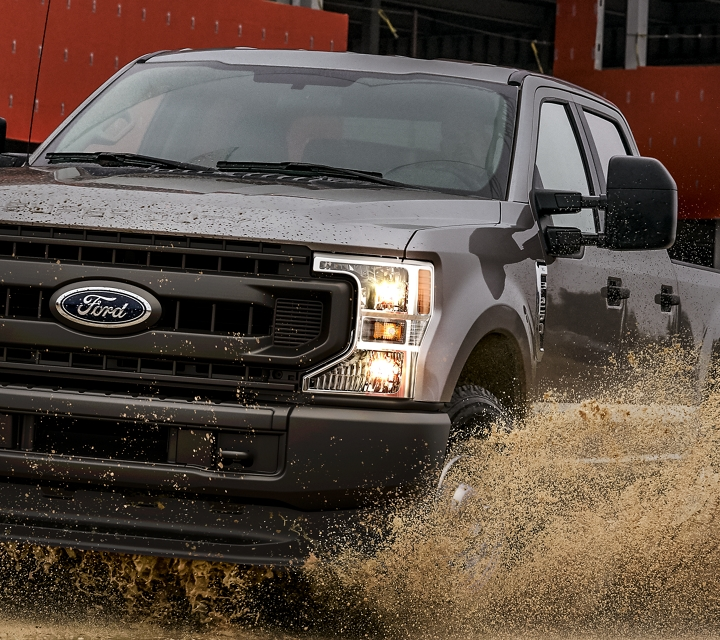 A 2020 Super Duty splashes through a puddle on a construction site