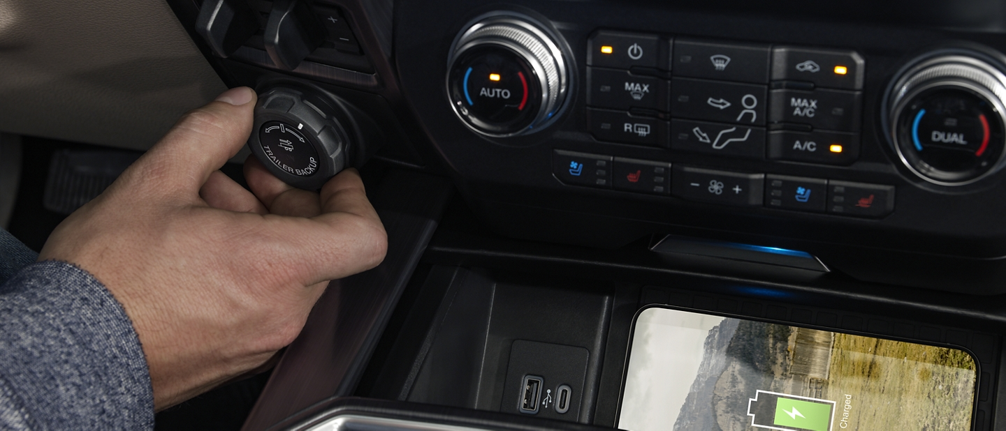Drivers hand engaging the Pro Trailer Backup Assist in the cab of a 2020 Super Duty