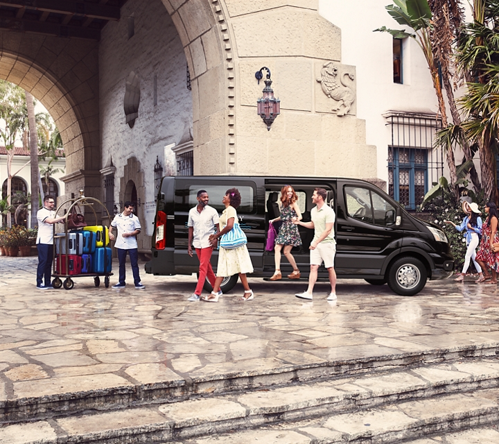 Tropical resort guests emerge from a transit passenger van