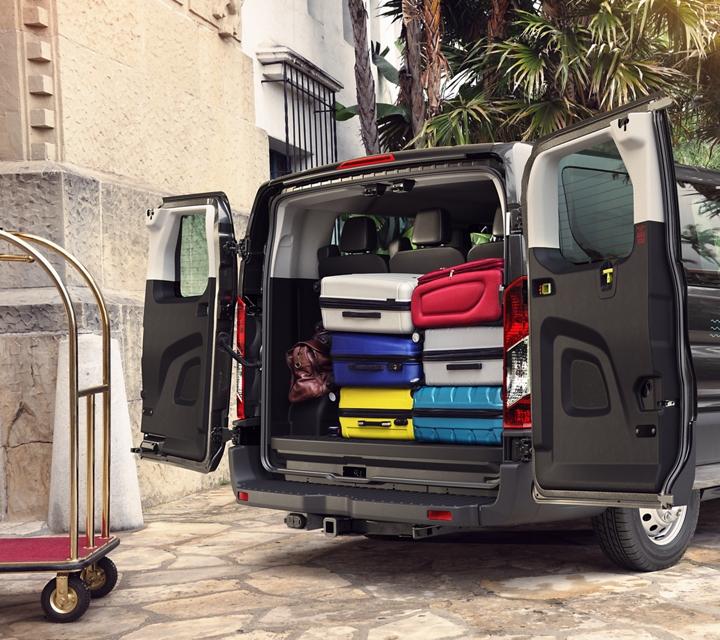 A resort bellhop unloads luggage from a transit passenger van