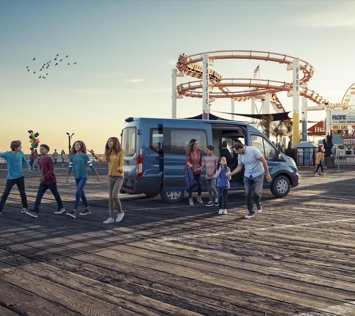 A large family arrives at an amusement park in a transit passenger van