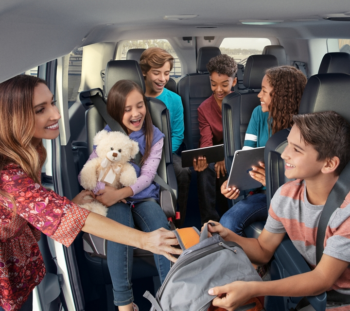 A family seated in the large interior of a transit passenger van