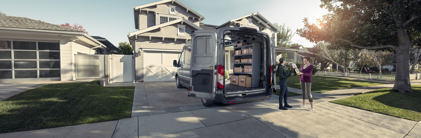 A package being delivered from the back of a ford transit cargo van