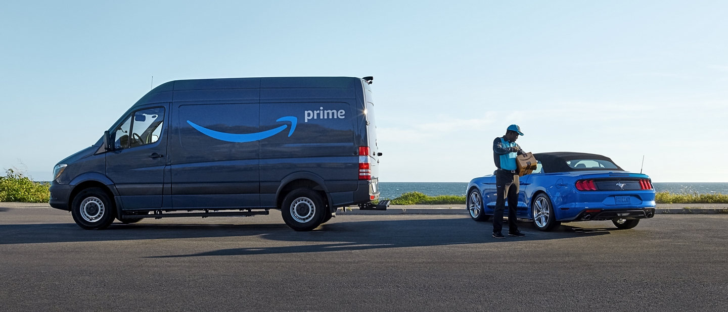 Amazon Prime delivery truck placing package in a Ford Mustang