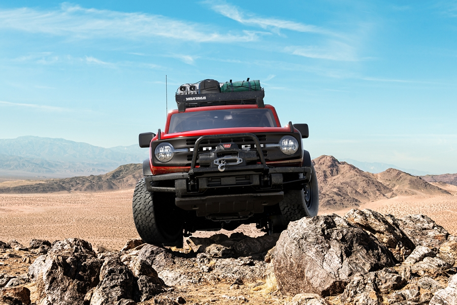 2021 Ford Bronco in Race Red driving over rocky terrain