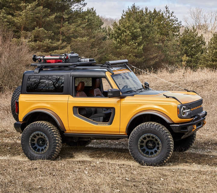 2021 Ford Bronco in Cyber Orange Metallic driving through woodland field