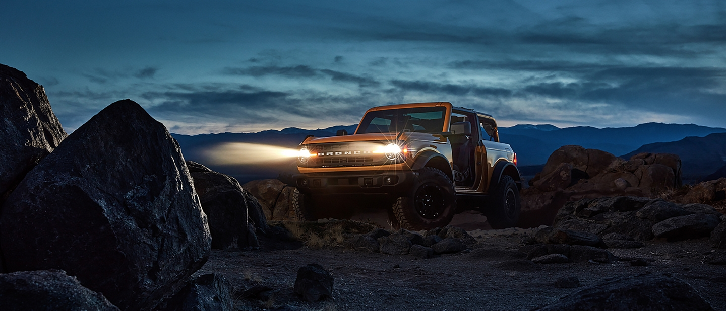 2021 Ford Bronco two door model in the desert at night with headlamps on