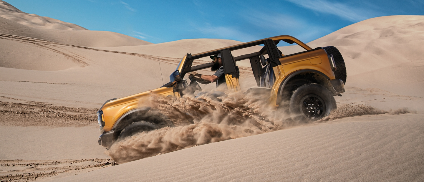 Profile view of 2021 Ford Bronco being driven through sand dunes