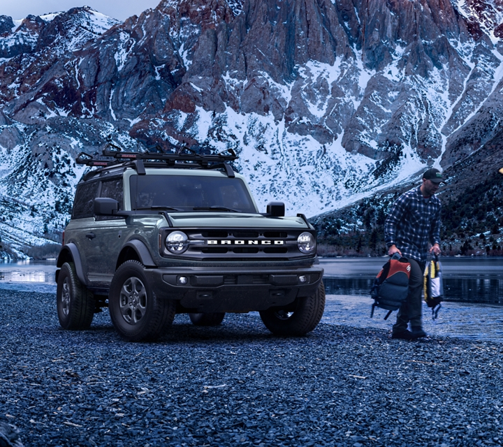 2021 Ford Bronco by a mountain lake with a couple of outdoor enthusiasts