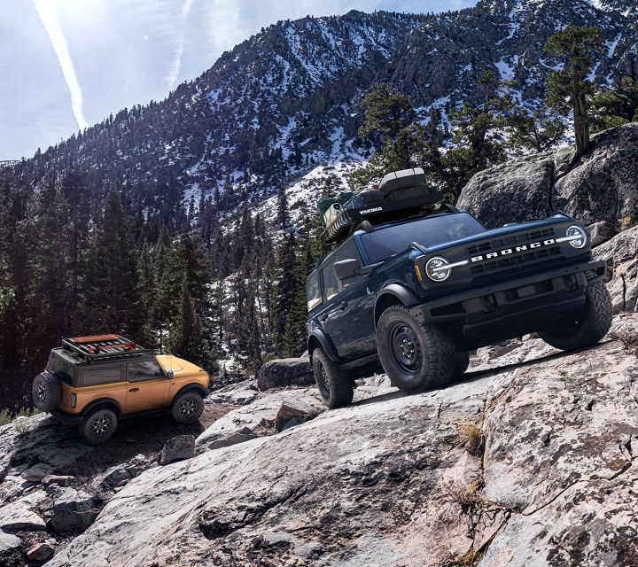 2021 Ford Bronco two door and four door models being driven through the wilderness