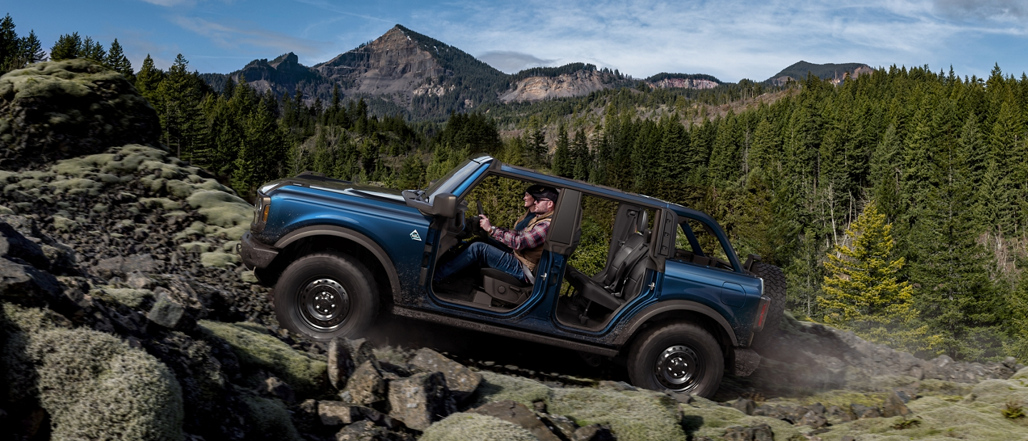 2021 Ford Bronco being driven uphill in the woods with the doors off