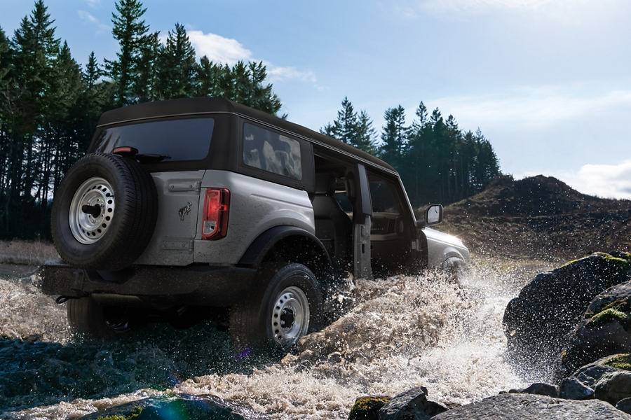2021 Ford Bronco 4 door driving through water in the woods
