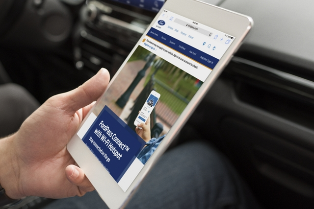 A passenger in the 2020 Ford EcoSport uses FordPass Connect with 4 G L T E Wi Fi hotspot on an electronic tablet