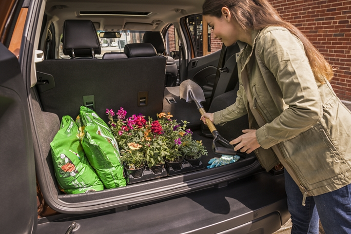 Woman loading gardening supplies into the extra cargo room provided by the 2020 Ford EcoSports fold flat second row seating