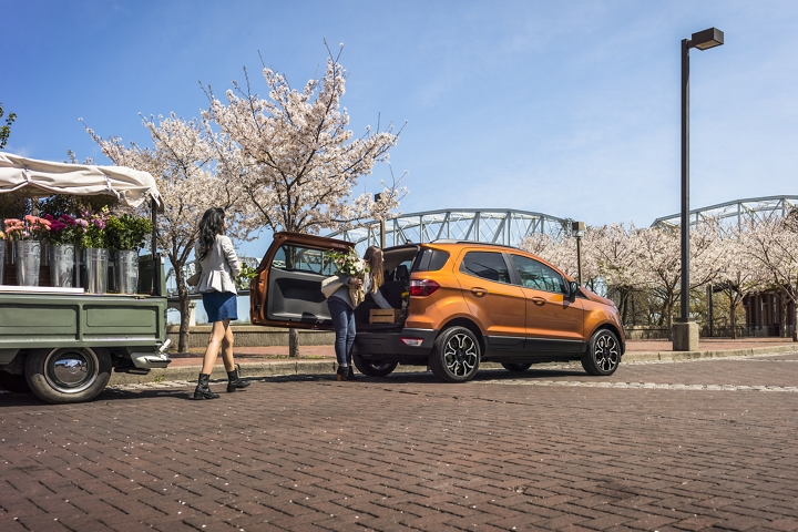 Two women loading flowers into a 2020 Ford EcoSport S E S in Canyon Ridge with rear swing gate open